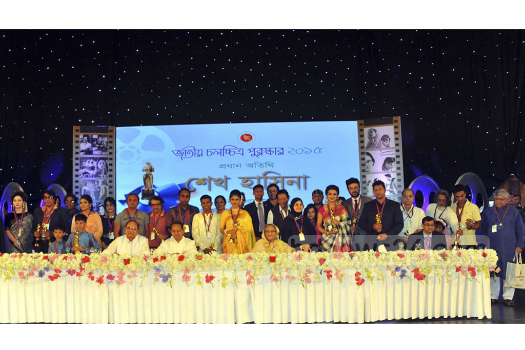 Winners of the National Film Award 2015 come together for photographs with Prime Minister Sheikh Hasina and other guests of the ceremony held in Dhaka on Monday.
