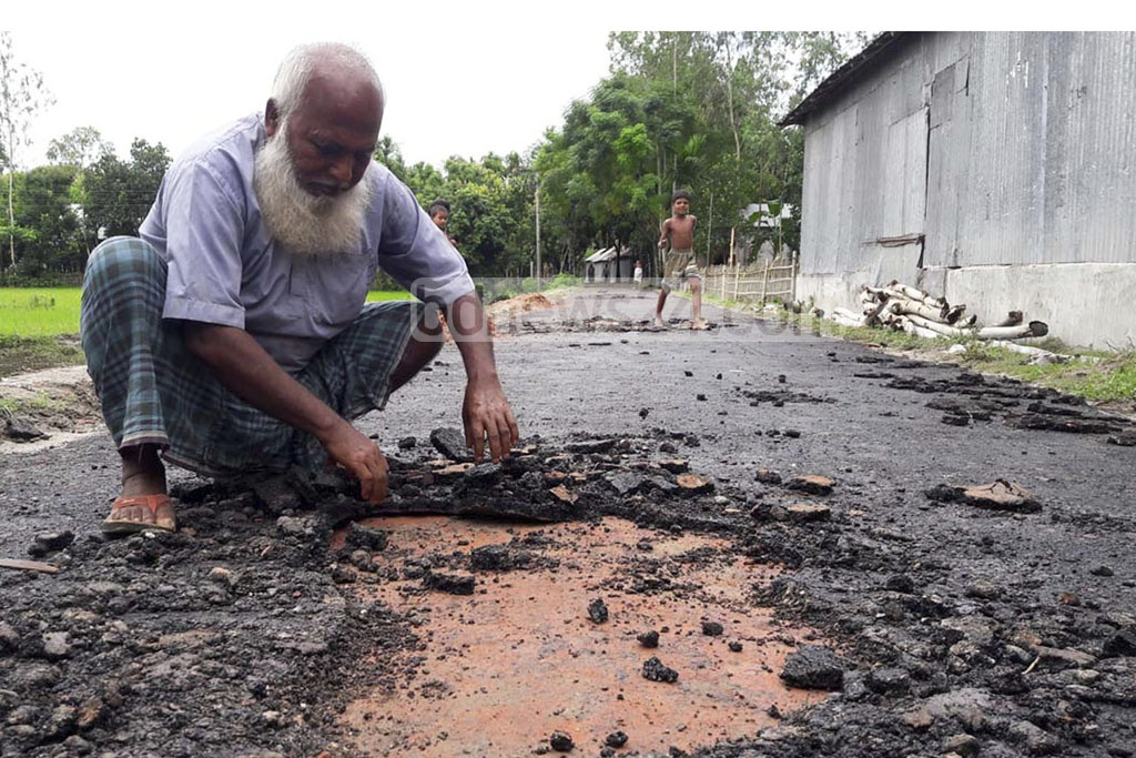 A man in Lalmonirhat's Aditmari looks at a road that began eroding five days after it was its construction was completed.