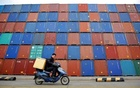 A man rides his motorcycle past shipping containers at the Port of Shanghai Feb 14, 2011. Reuters File Photo