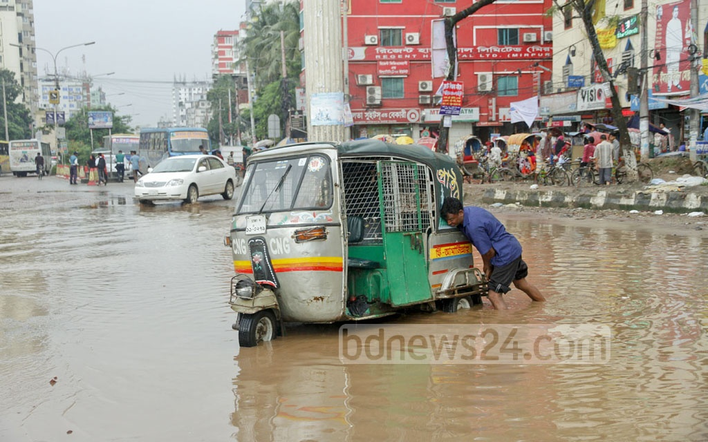 An autorickshaw driver struggles to pull out his vehicle from a hole that was not visible due to the rainwater submerging a Mirpur street. Photo: tanvir ahammed