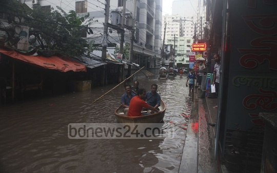 People use a boat to commute on a submerged street at Dhaka's Paltan following ​Wednesday's ​day-long heavy rains.​