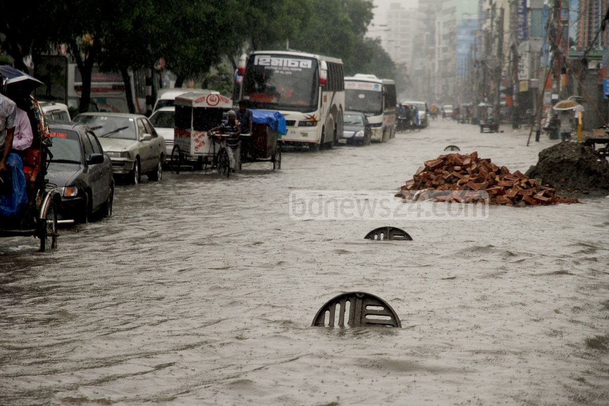 Manholes are left open to drain water submerging the road through Mirpur's Kazipara, but only a part of their lids appear above the surface amid heavy rain on Wednesday. Photo: tanvir ahammed