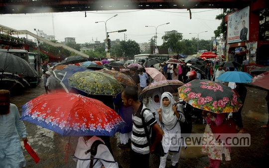 People waiting for buses at Mirpur-10 hold umbrellas overhead for protection against heavy rains. Photo: tanvir ahammed
