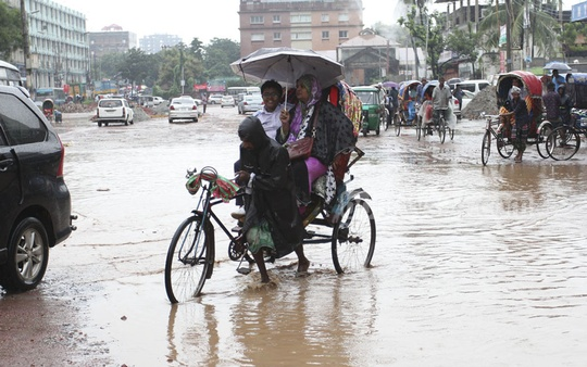 A rickshaw driver struggles to take passengers over the waterlogged bus stand area at Mirpur-12. Photo: asif mahmud ove