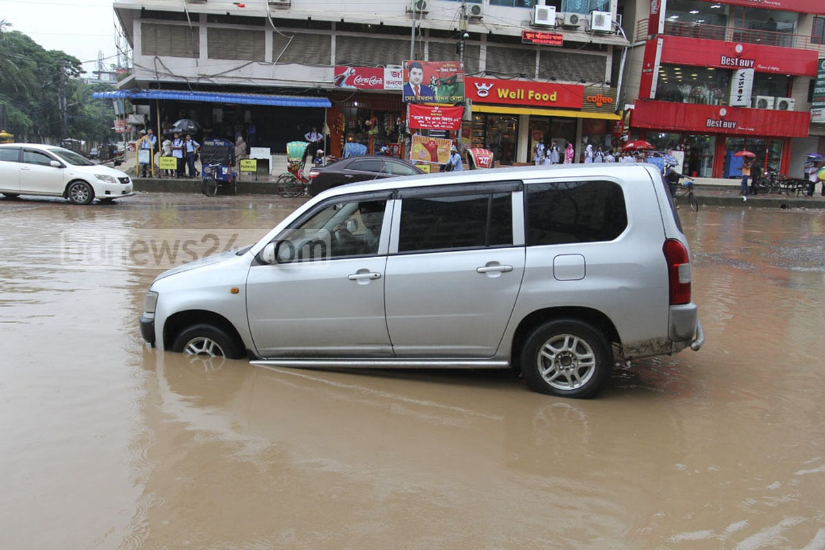 Commuters struggle to cross the waterlogged bus-stop area at Mirpur-12. Photo: asif mahmud ove