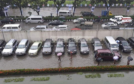 A row of vehicles parked inside the Secretariat amid heavy rain.