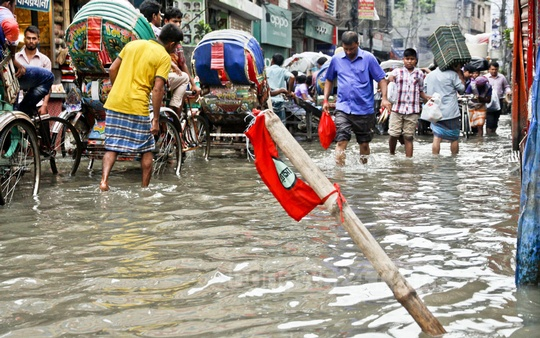 Dhaka WASA puts a red sign on a bamboo to mark an uncovered manhole on waterlogged Nazimuddin Road in Old Dhaka. Photo: tanvir ahammed