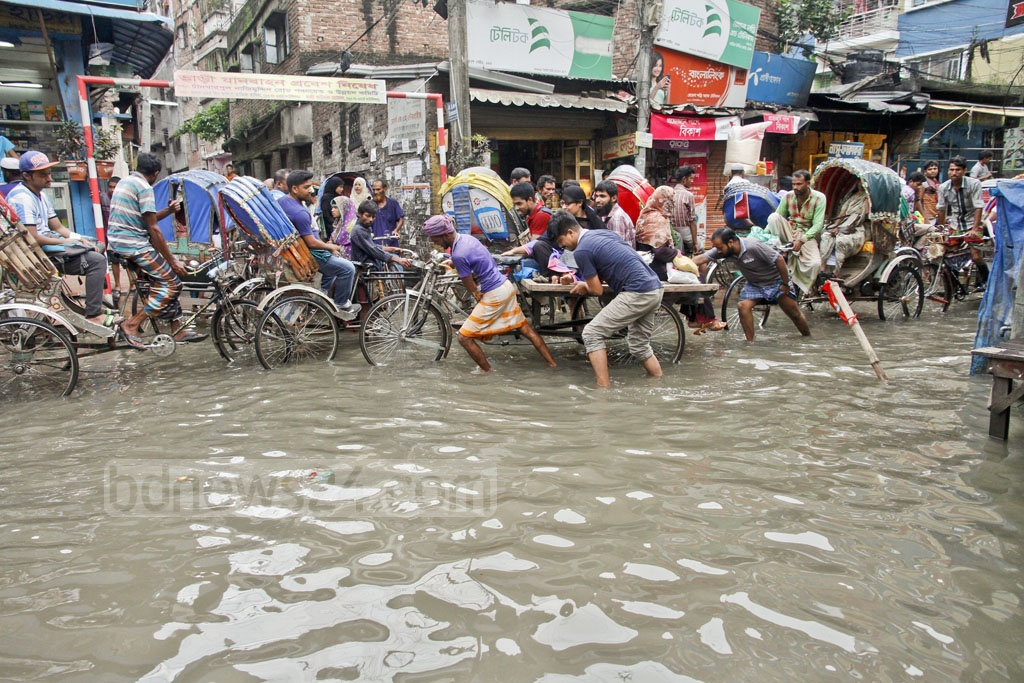 The people of Nazimuddin Road in Old Dhaka do not know when their sufferings for waterlogging will ease. Rain stopped a day ago, but the water is still to go away from the area. The photo was taken on Thursday. Photo: tanvir ahammed