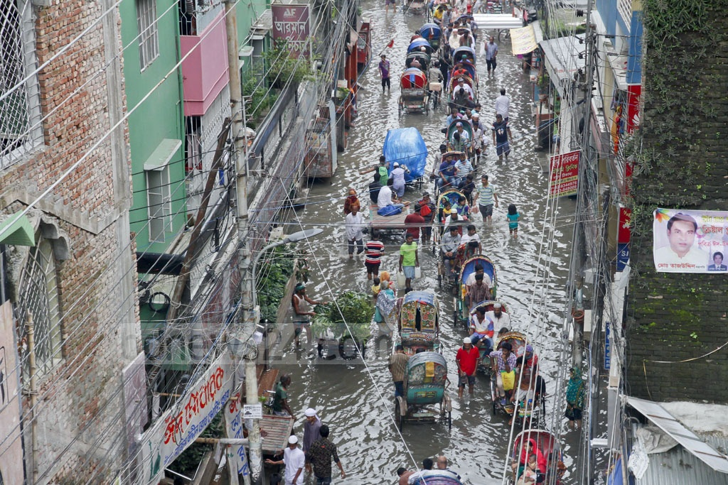 People slosh through water in front of the houses and shops on Nazimuddin Road in Old Dhaka as the authorities fail to drain out water a day after rain on Thursday. Photo: tanvir ahammed