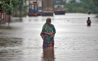 A woman wades through a road flooded by heavy rain in Ahmedabad, India, Jul 24, 2017. Reuters