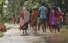 A woman (C) looks on as she walks with others to a safer place through a flooded road after incessant rains at Bullut village in Kamrup district in Assam, June 12, 2015. Reuters