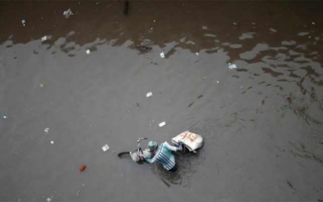 A man pushes his bicycle through a water-logged street after heavy rains in Ahmedabad, India.