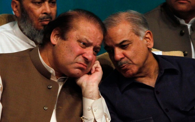 FILE PHOTO - Nawaz Sharif talks with his brother Shahbaz Sharif before addressing his party members who were voted to political posts in the general election, during a function in Lahore May 20, 2013. Reuters