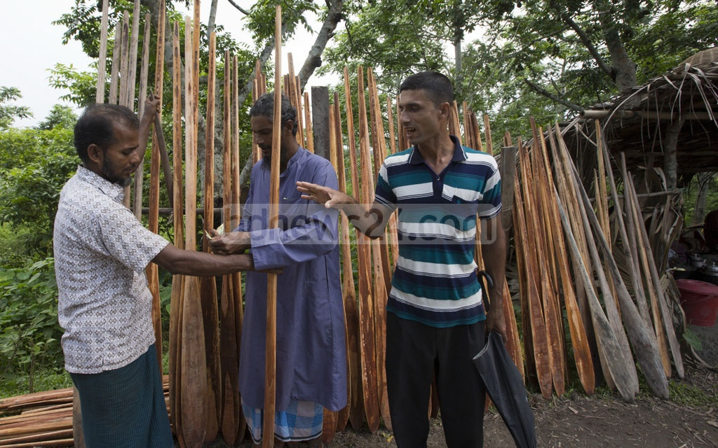 A buyer checking out oars at the market on Aatghar canal.