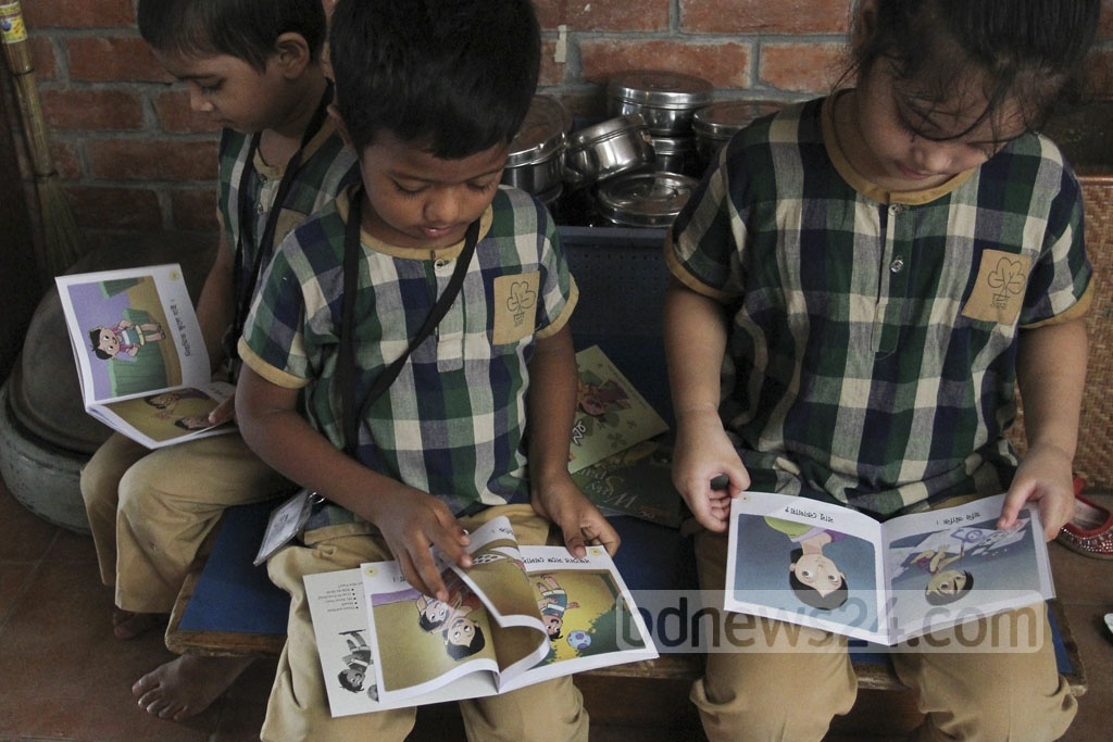 Children reading books at the book fair at Chhayanaut on Sunday. Photo: asif mahmud ove