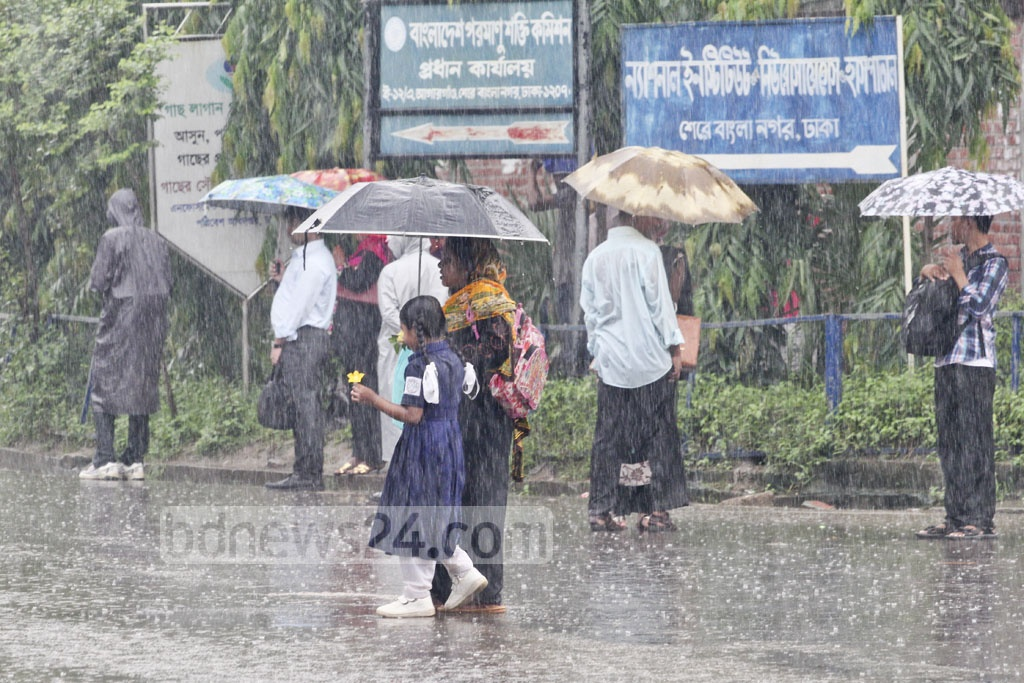 People in Dhaka continue their daily lives amid heavy rain. Photo taken from Agargaon on Sunday. Photo: asif mahmud ove