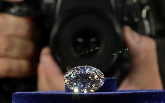 A photographer takes a picture of the main 51.38-carat diamond on display during Russian miner Alrosa's presentation of the Dynasty polished diamonds collection in Moscow, Russia, August 1, 2017.
