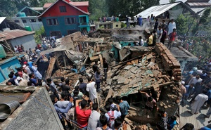 People stand on the rubble of a house after it was damaged during a gunbattle between militants and Indian security forces in Hakripora in south Kashmir's Pulwama district August 1, 2017. Reuters