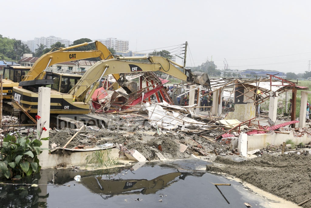 RAJUK demolishes illegal structures along the Purbachal road in a drive on Thursday.