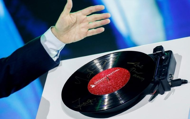 A record signed by representatives of the Recording Academy, Bravo Entertainment and China Music Vision spins on a player during a ceremony in Beijing marking a Chinese partnership to create the Grammy Festival China, August 3, 2017. Reuters