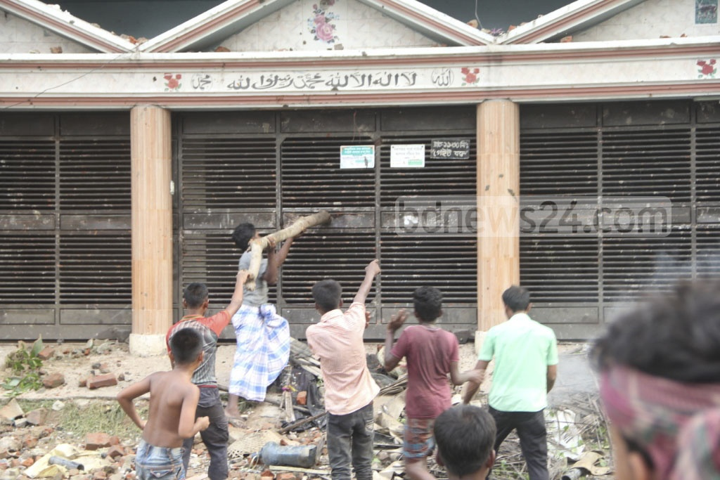 Locals agitated at the alleged murder of a house help break the gate of the house at Banasree in Dhaka on Friday.