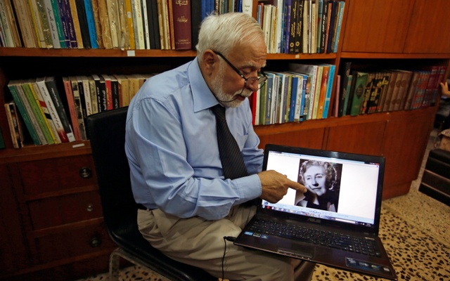 Doctor and historian Ibrahim Khalil Al-Allaf refers to Agatha Christie picture during the interview with Reuters in Mosul, Iraq Jul 30, 2017. Reuters
