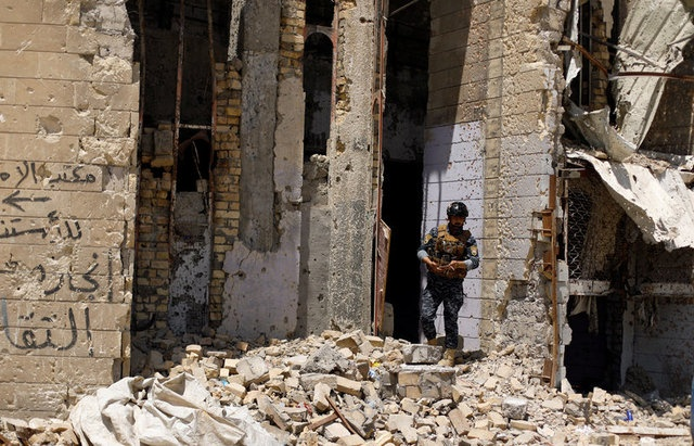 A member of Iraqi federal police stands guard in the destroyed Old City of Mosul, Iraq August 5, 2017. REUTERS/Suhaib Salem
