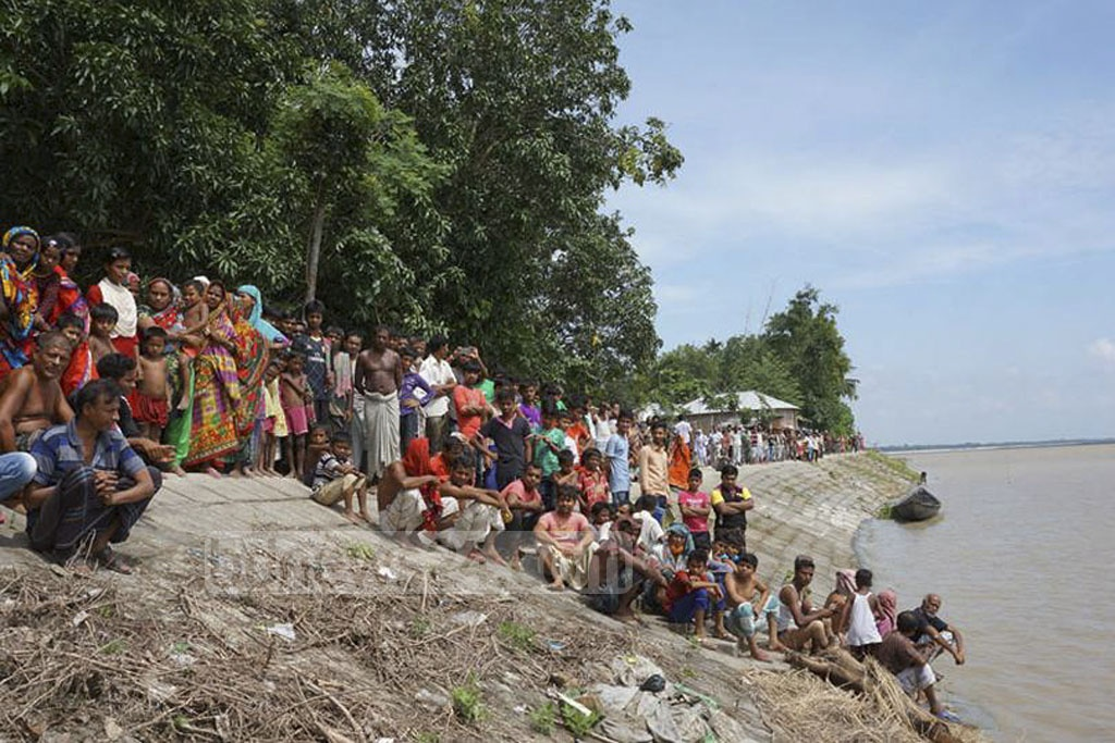 Residents of Pabna's Ishwardi gather on the banks of Padma River on Tuesday after one of the two missing schoolboys' body was recovered.