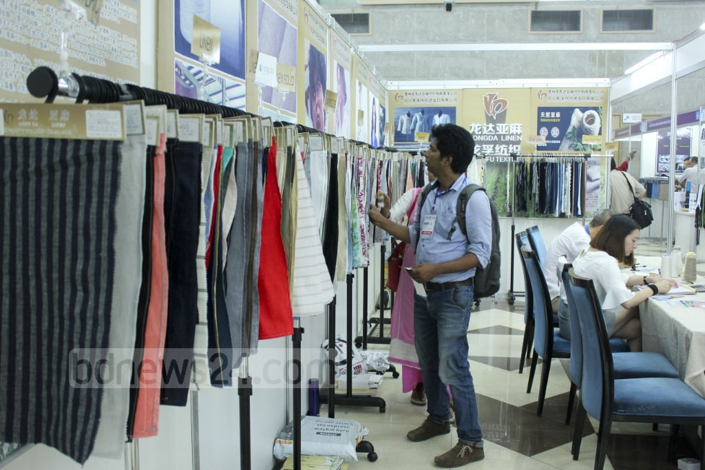 Visitors at a stall at Textech Bangladesh, which is an international exhibition of textile and garment machines, cotton and chemical agents used in textile industry, being held at the International Convention City Bashundhara in Dhaka.