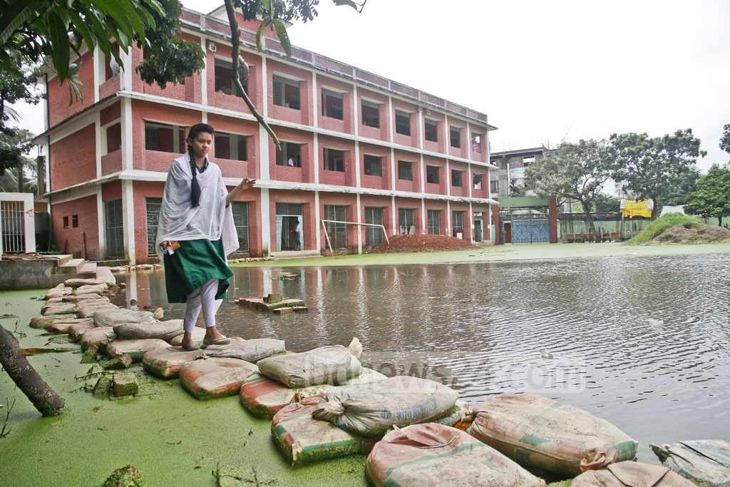 A student of Dogair Rustom Ali High School walks on sandbags dumped on the school premises for movement of students amid clogged rainwater.