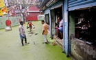 A lane in Dogair, Demra in capital Dhaka is submerged by clogged water that has gone greenish with dirt and toxins dissolved in it. Businesses and commuters are forced to continue with their daily activities amidst the hazard.