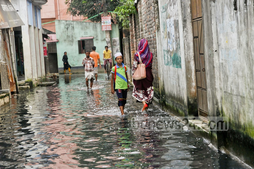People walk through the dirty, foul-smelling clogged rainwater every day in Dogair, Demra. The situation has remained unchanged there for three months now.