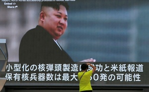 A man takes a photo in front of a monitor showing news of North Korea's fresh threat in Tokyo, Japan, August 9, 2017. Reuters