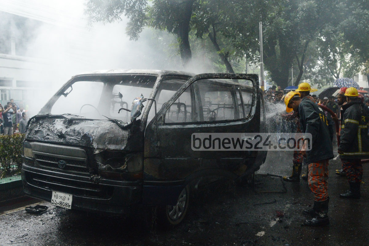 Firefighters spray water on a microbus that cause fire while passing the Chittagong Club area on Friday. Photo: suman babu
