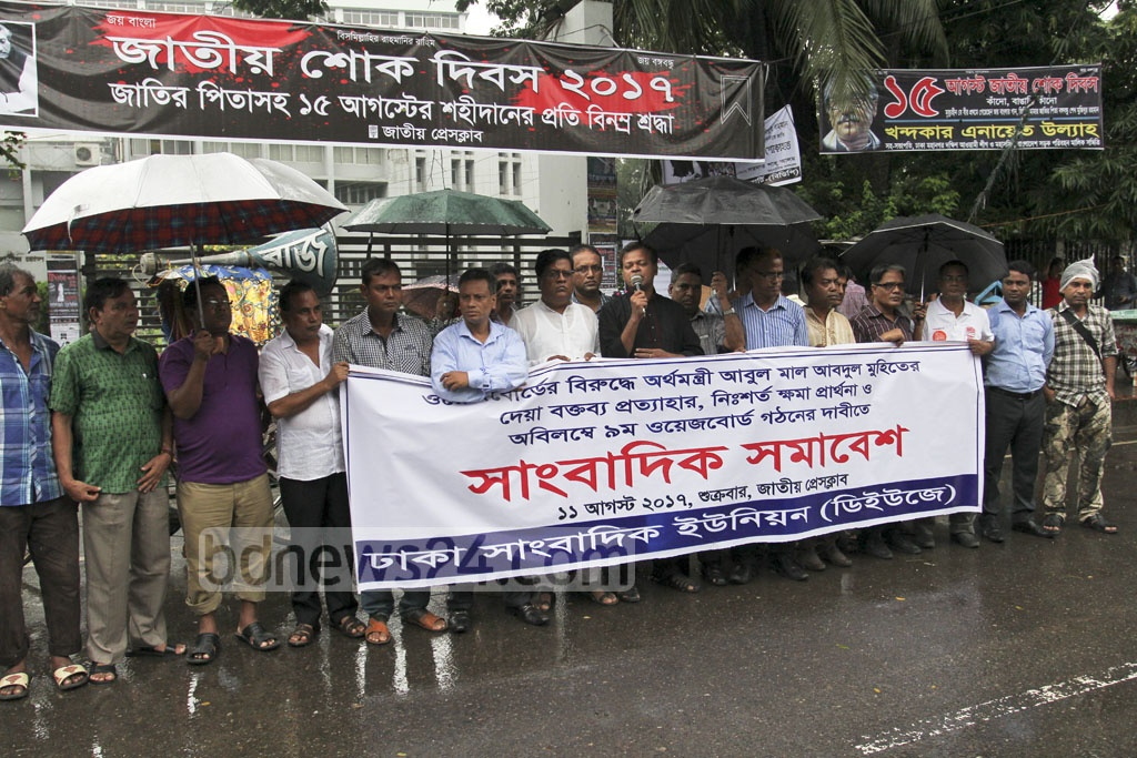 Dhaka Union of Journalists holds a demonstration outside Dhaka's National Press Club on Friday. Its members demanded a new pay scale for journalists, while criticising the finance minister for his recent remark against its formation.