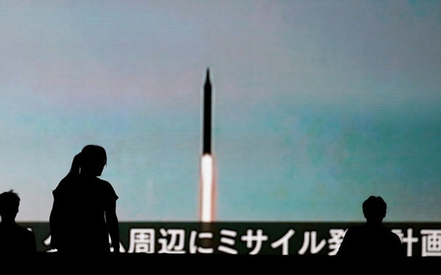People walk in front of a monitor showing news of North Korea's fresh threat in Tokyo, Japan, August 10, 2017. Reuters