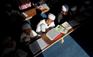 FILE PHOTO: Children belonging to Rohingya Muslim community read the Koran at a madrasa, or a religious school, at a makeshift settlement, on the outskirts of Jammu May 6, 2017. Reuters