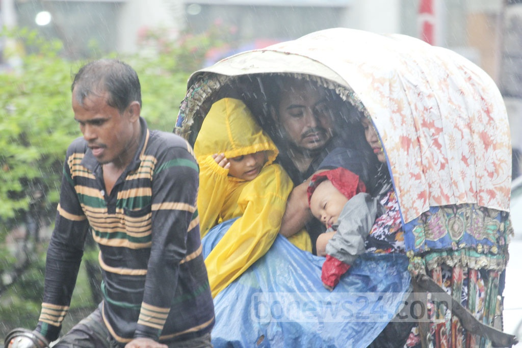 A family had to take the rickshaw ride amid incessant rain on Saturday. The picture is taken from Dhanmondi areas of the capital.
