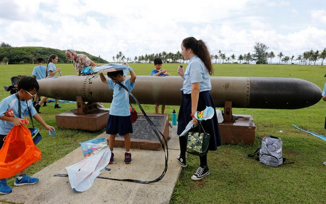 Pupils play near the World War II remnants of a torpedo at the Asan Memorial Park on the island of Guam, a US Pacific Territory, August 11, 2017. Reuters