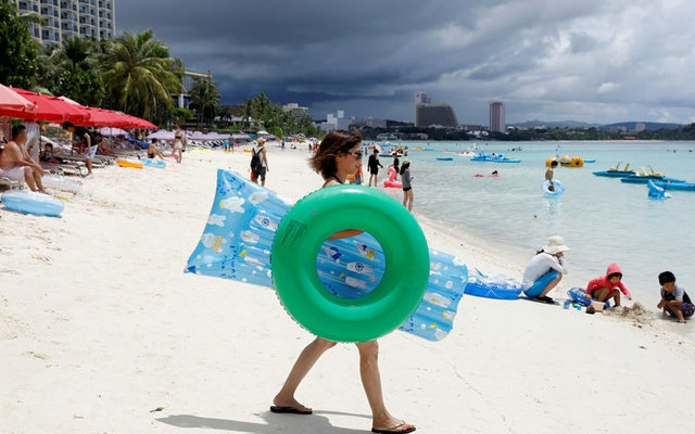 Tourists frolic along the Tumon beach on the island of Guam, a US Pacific Territory, August 10, 2017. Reuters