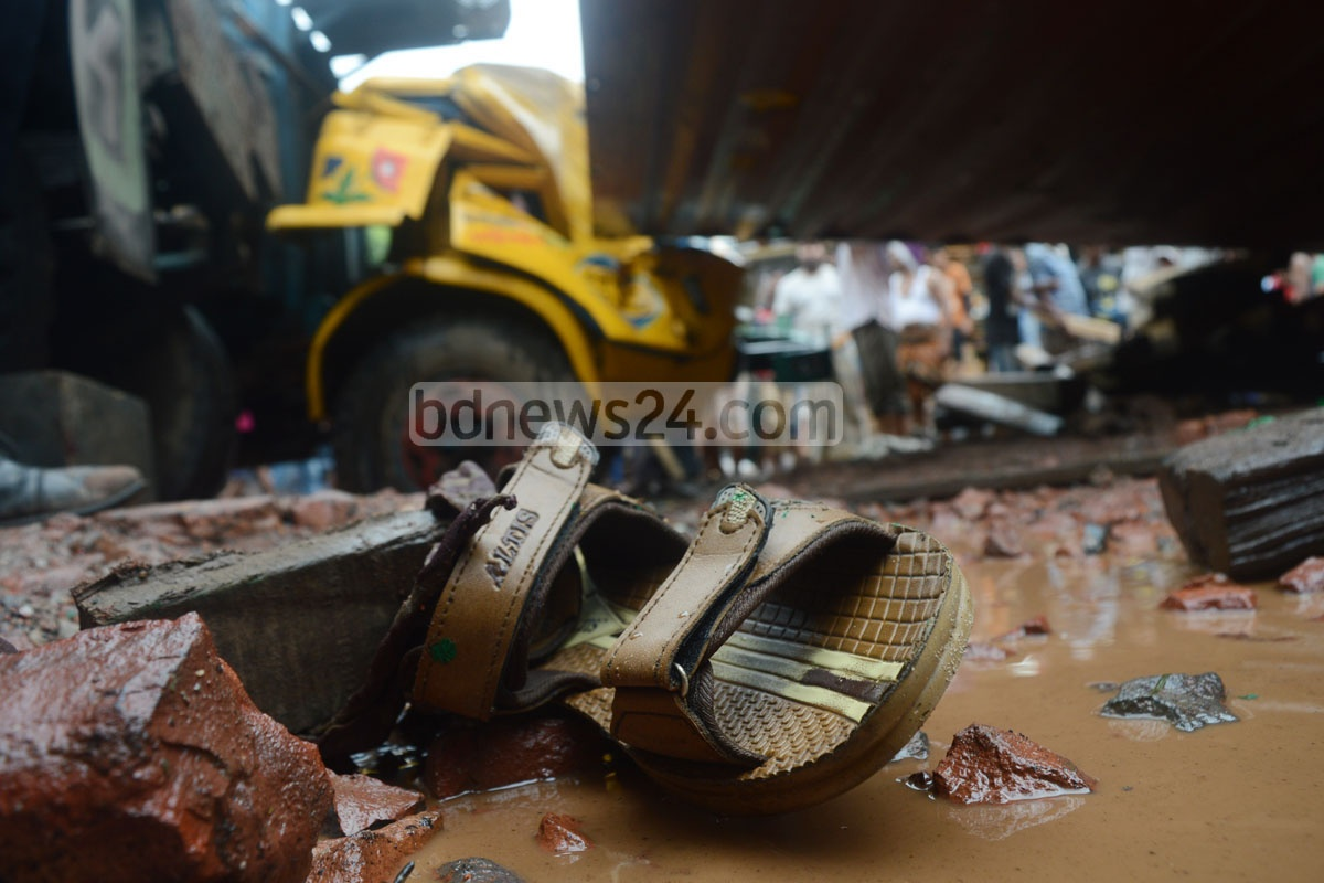 Two people were killed and another two injured after a freight trailer overturned on a broken road in Chittagong's Neemtala intersection, crushing an autorickshaw on Sunday. Photo: suman babu