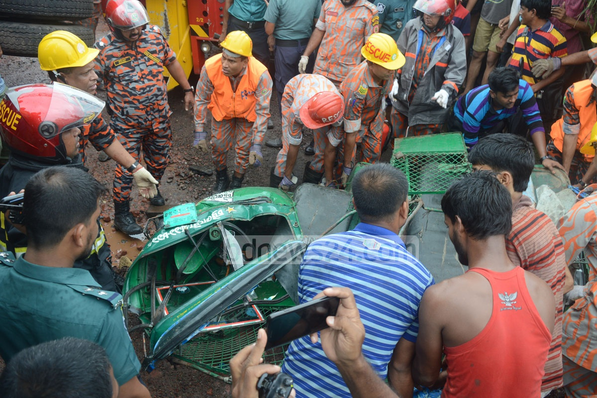 Fire service personnel conduct rescue operations after a freight trailer overturned on a broken road in Chittagong's Neemtala intersection, crushing an autorickshaw on Sunday. Photo: suman babu