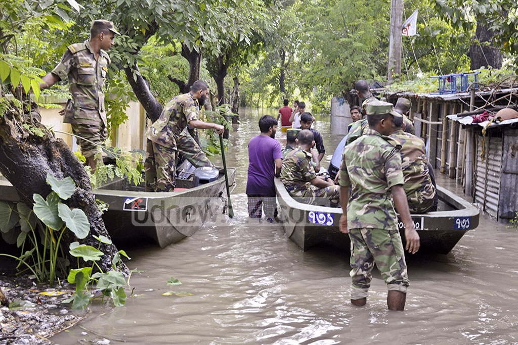 Army soldiers evacuate villagers trapped in floodwaters at Dinajpur.