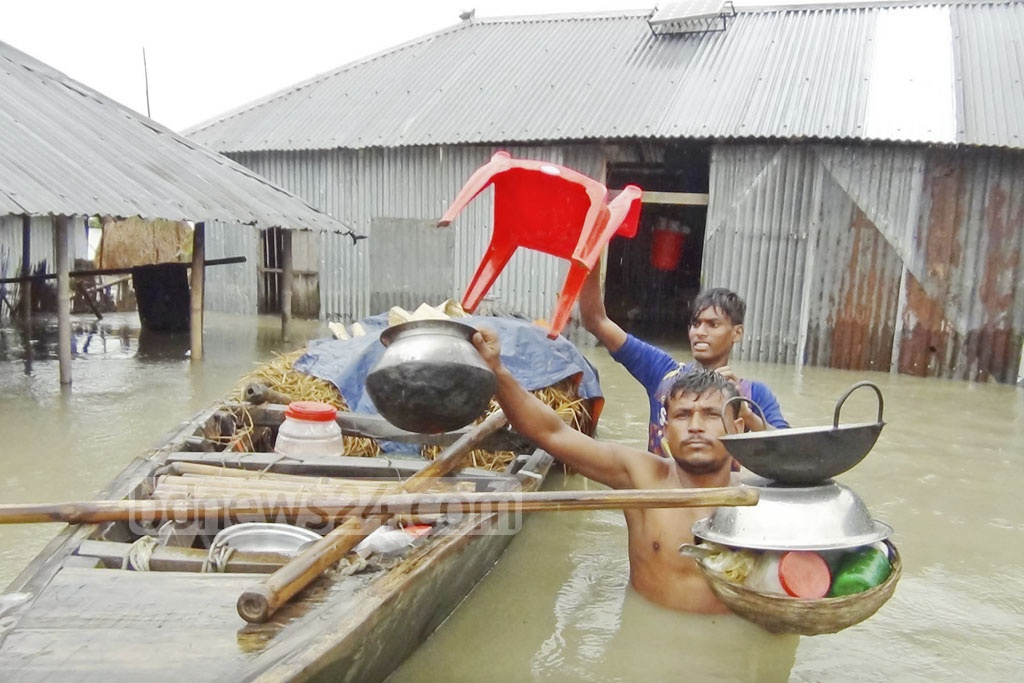 As floodwaters submerge homes, people gather their belongings for evacuating to higher grounds. Photo taken at Jogmohom Char of Kurigram's Sadar Upazila on Sunday.