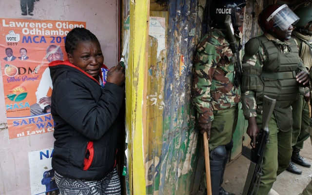A woman cries as she stands behind policemen during clashes between supporters of opposition leader Raila Odinga and policemen, in Kibera slum, in Nairobi, Kenya Aug 12, 2017. Reuters