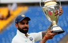 India's captain Virat Kohli holds the trophy for photographs after they won the match and test cricket series against Sri Lanka. Reuters