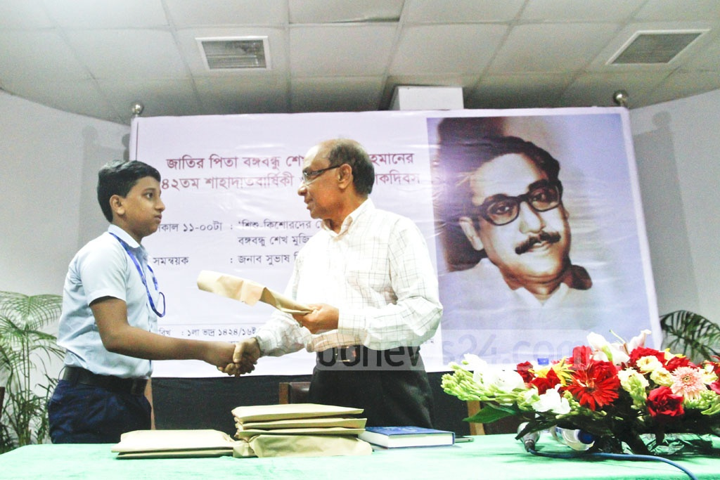 Bangla Academy Director General Professor Shamsuzzaman Khan distributing books at an event on Wednesday for school students. Photo: tanvir ahammed