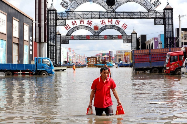 eople walk through a flooded area at a building materials market in Harbin, Heilongjiang province, China August 7, 2017. Picture taken August 7, 2017. CNS/Wang Shu via REUTERS ATTENTION EDITORS - THIS IMAGE WAS PROVIDED BY A THIRD PARTY. CHINA OUT.