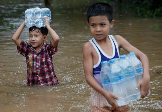 Boys carry water bottles distributed by an aid organization during the flood in Kyaikto township, Mon state, Myanmar July 22, 2017. REUTERS/Soe Zeya Tun