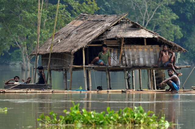Villagers take shelter at a partially submerged house following floods at Baghmari village in Nagaon district, in the northeastern state of Assam, India August 15, 2017. REUTERS/Anuwar Hazarika TPX IMAGES OF THE DAY